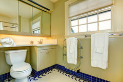Bright yellow bathroom with blue tile floor Stock Photos