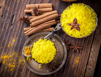 Bright yellow boiled rice with turmeric and. Aromatic spices on a dark wooden background in old vintage metal bowl Stock Images