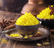 Bright yellow boiled rice with turmeric and. Aromatic spices on a dark wooden background in old vintage metal bowl. selective Focus Royalty Free Stock Photos