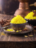 Bright yellow boiled rice with turmeric and. Aromatic spices on a dark wooden background in old vintage metal bowl. selective Focus Royalty Free Stock Photography