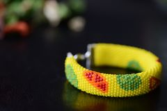 Bright yellow bracelet with citrus print on a dark background Royalty Free Stock Photography