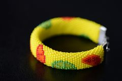 Bright yellow bracelet with citrus print on a dark background Stock Images
