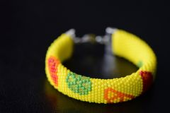 Bright yellow bracelet with citrus print on a dark background Royalty Free Stock Images