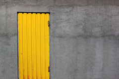 Bright yellow closed door in a gray wall. Background image of bright yellow door in a gray wall Royalty Free Stock Photography