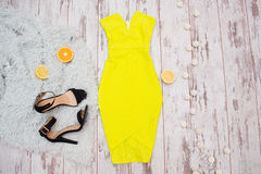 Bright yellow dress, black shoes, and citrus on the fur. Lanterns, Light wooden background. Fashionable concept Royalty Free Stock Image