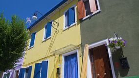 Bright yellow dwelling house neighboring well-kept colorfully painted buildings