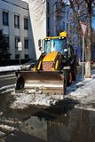 Bright yellow excavator tractor cleaning snow on the road along houses, front view, snowy winter in Kharkiv. Ukraine royalty free stock photo