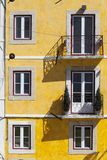 Colorful building with windows. Bright yellow facade with square symmetrical windows in Lisbon, Portugal stock photo