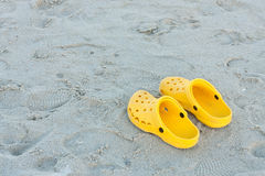Bright yellow flip-flops on sand beach Royalty Free Stock Photography