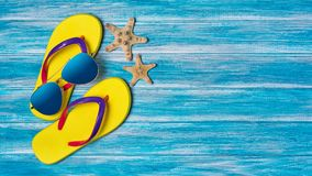 Bright yellow flip flops with sunglasses and starfish as concept of vacation time. Top view on bright yellow flip flops with sunglasses and starfish as concept royalty free stock photo
