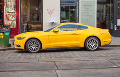 Bright yellow Ford Mustang 2015 car stands in city Stock Images