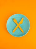 Bright yellow fork and knife Royalty Free Stock Image