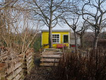 Bright yellow garden hut or small rustic home Stock Photos