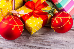 Bright yellow gift with a red bow. Red balls and gifts on wooden background. Christmas symbols Stock Photography