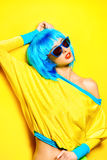 Bright yellow. Bright glamorous girl in vivid clothes and a wig alluring over yellow background. Beauty, fashion. Cosmetics, hairtsyle. Optics, eyewear Stock Photos