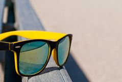 Bright yellow glasses with a black frame and multi-colored lenses lie on the bench. In reflection, the beach, the beach, the blue Stock Image