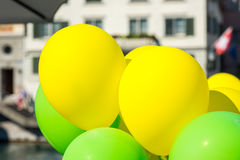 Bright yellow and green balloons on a city street Royalty Free Stock Photo