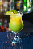 Bright yellow-green cocktail garnished with lime. stock photos