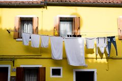 Bright yellow house with shutters and washing hanging out on the island of Burano, Venice.