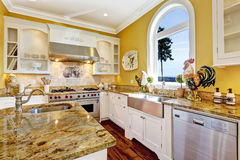 Bright yellow kitchen room with granite tops and arch window Stock Images