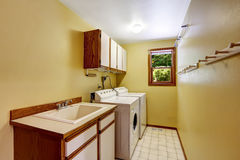 Bright yellow laundry room with cabinets and sink Stock Photos