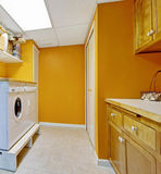 Bright yellow laundry room interior Stock Images