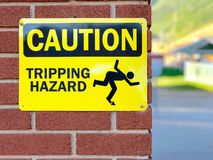 Humorous yellow caution sign on red brick wall with stick man illustrating tripping hazard. Bright yellow metal sign posted on red brick wall, text saying royalty free stock photo