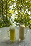 Bright yellow and milkshakes in glasses with handles and tubules on a white marble table on a blurred background of green trees. A bright yellow and milkshakes stock photos