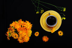 Bright Yellow Mocha Cup and Orange Flowers. Bright yellow vintage mocha cup with coffee.  The coffee set is surrounded by yellow flowers on black.  A bouquet of Royalty Free Stock Photos