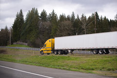 Bright yellow modern semi truck trailer on fencet exit to highway road stock photos