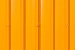 Bright yellow-orange corrugated painted metal wall background. Stock Image