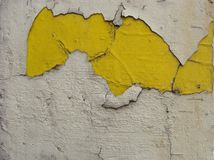 Bright yellow paint showing through under white peeling paint Stock Photo