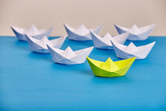 Bright yellow paper ship leading white ones based on blue against light background. Handmade and origami. Trip around the world. Travel and transportation Royalty Free Stock Image