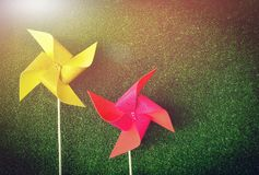 Bright yellow and pink pinwheels on green grass background. Royalty Free Stock Photos