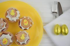 Flat lay spring time Easter plate with homemade baked mini cream cakes and egg decorations. Bright yellow plate on a white wood table and filled with home made royalty free stock images