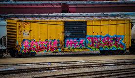 Bright yellow railroad car tagged with graffiti. Bright yellow railroad car sitting on tracks with brightly colored graffiti tags Stock Photo