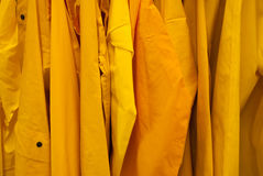 Bright Yellow rain jackets background coat. A close up of yellow rain jackets hanging on a rack Royalty Free Stock Images