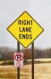 Right Lane Ends Warning Sign. A bright yellow right lane ends warning sign shows against a rural background Royalty Free Stock Images