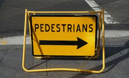 Bright yellow road sign with arrow indicating pedestrian bypass direction stock images