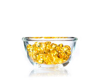Bright yellow soft gel pills in clear glass bowl Royalty Free Stock Photos