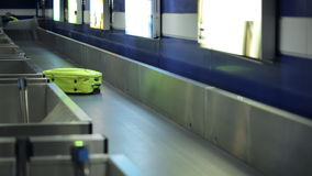 Bright yellow suitcase is traveling on conveyor belt in airport. It has just been loaded from luggage of aircraft for being delivered to his owner. This is stock footage
