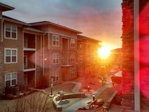 Bright sun beaming through apartment complex. Bright yellow sun beaming through a modern metro apartment complex Royalty Free Stock Photography