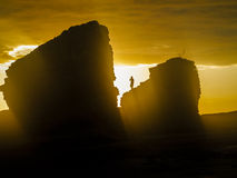 Bright yellow sun on the sea stacks with silhouette of a person standing on the top of a rock Stock Photos