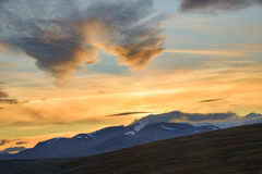 Bright yellow sunset over the highest swedish mountains in Sarek. Trekking through Sarek national park is a awesome experience. This view is from a mountain top royalty free stock image