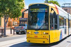 Bright yellow tramway on Moseley square. Glenelg, Australia. Glenelg, Australia - November 13, 2017: Bright yellow tramway with friendly driver waving his hand Royalty Free Stock Images