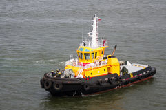 Bright yellow tug boat in the harbor Royalty Free Stock Photography