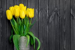 Bright yellow tulips in silver vase on black vintage wooden table. Flat lay, top view stock photo