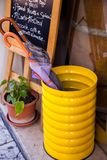 Bright yellow umbrella stand with plant. A picture perfect bright yellow umbrella stand in front of a daily specials board sends a message of welcome to passers Royalty Free Stock Image