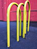 Bright Yellow Vehicle Barriers. Bright yellow metal hoop vehicle protective barriers on sidewalk or pavement stock photos