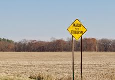 Watch for Children Warning Sign. A bright yellow watch for children warning sign shows against a rural background Royalty Free Stock Images